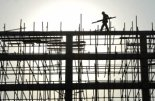 A labourer walks on the scaffoldings at a construction site in Xiangfan, central China's Hubei province November 16, 2006. China's racing economy is likely to shift to a lower gear next year as the government takes further cooling measures to reduce a ballooning trade surplus and excess cash in the banking system. CHINA OUT REUTERS/Stringer (China)